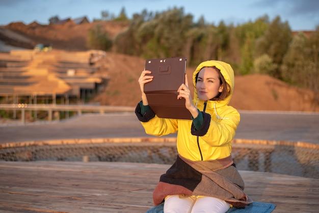 Ritratto di una donna in una giacca gialla con una coperta su un molo di legno, fotografato su un tablet sunrise