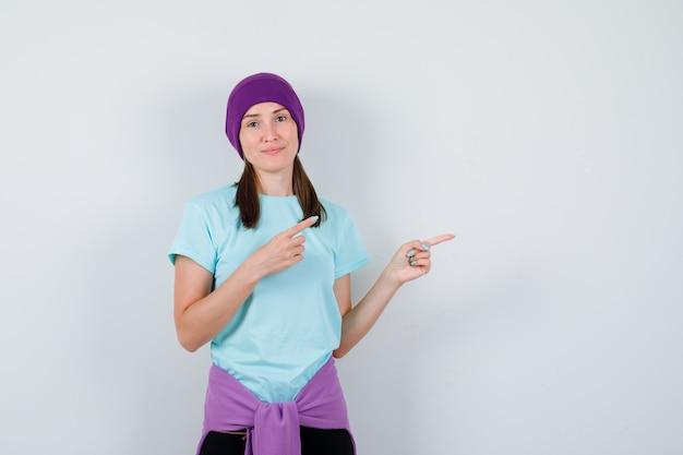 Ritratto di una donna meravigliosa che punta verso il lato destro in camicetta, berretto e sembra fiduciosa in vista frontale