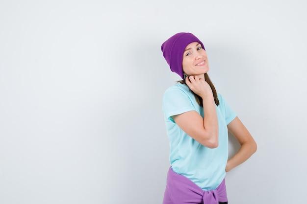 Ritratto di una donna meravigliosa che si tocca la pelle in camicetta, berretto e sembra affascinante vista frontale