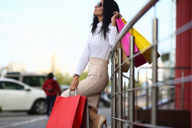 Ritratto della donna meravigliosa che sta emporio vicino. bella femmina in abbigliamento stile business e accessori in possesso di sacchetti colorati negozio.