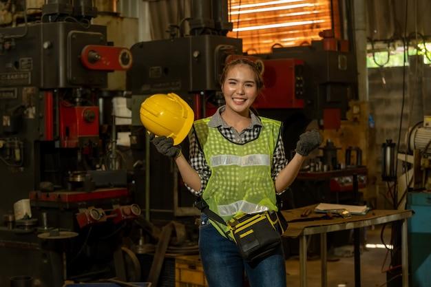 Ritratto di un lavoratore nel casco che lavora in fabbrica con vari processi di lavorazione dei metalli