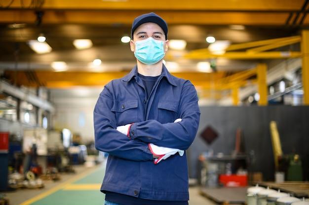 Ritratto di un operaio in uno stabilimento industriale che indossa una maschera, concetto di coronavirus
