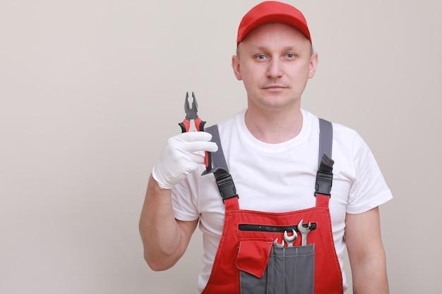 Ritratto di un operaio in uniforme rossa, cappuccio e pinze della holding del guanto bianco