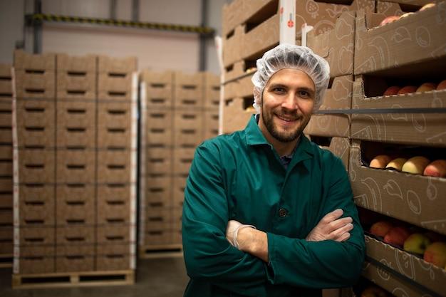 Ritratto di lavoratore in piedi da casse di frutta mela nel magazzino di fabbrica di alimenti biologici.