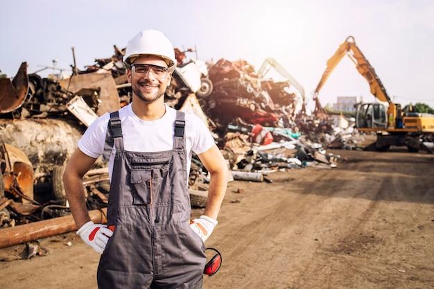 Ritratto di lavoratore in piedi nel deposito di rifiuti di metallo con gru di sollevamento rottami di metallo per il riciclaggio.
