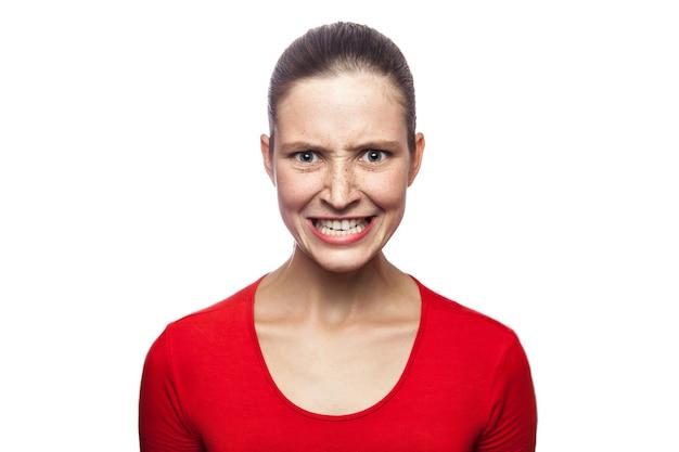 Ritratto di donna arrabbiata preoccupata in maglietta rossa con lentiggini