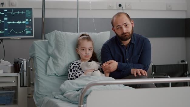 Ritratto di padre preoccupato che tiene la mano della figlia malata ricoverata che guarda nella telecamera