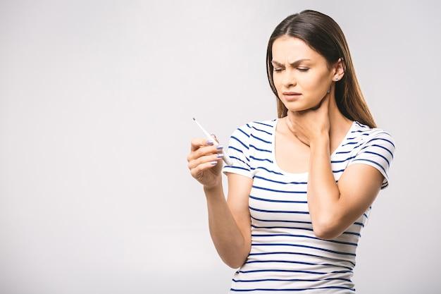 Ritratto di una giovane bella donna preoccupata che controlla la sua temperatura