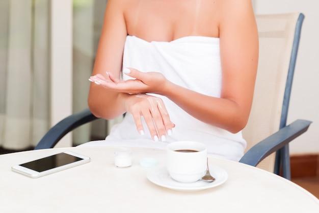 Il ritratto della donna avvolta in asciugamano con le bende dell'occhio sta applicando la crema sulle sue mani che si siedono al tavolo sulla terrazza dell'hotel. concetto di trattamento di bellezza