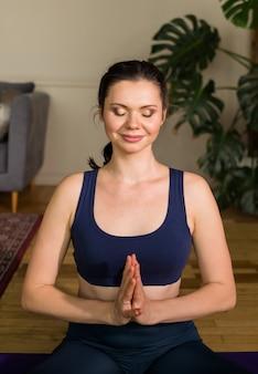 Ritratto di una donna di yoga con le mani giunte e gli occhi chiusi in una stanza