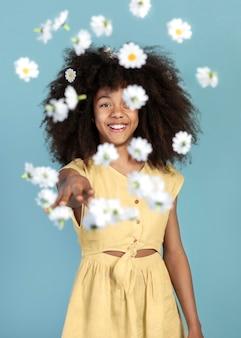 Ritratto di giovane ragazza adorabile in posa con i fiori di camomilla