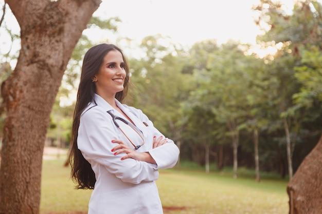 Ritratto di giovane femmina adulta medico o infermiere che indossa camice da laboratorio e stetoscopio all'esterno