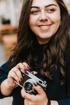 Ritratto di giovane ragazza adulta con fotocamera vintage all'aperto