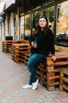 Ritratto di una giovane ragazza adulta con una tazza di caffè vicino a un bar in un bel tempo autunnale