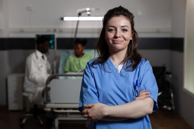 Ritratto di giovane adulto con occupazione infermiera in corsia ospedaliera. donna caucasica che lavora come personale di assistenza medica presso la clinica di recupero. persona con l'uniforme in piedi che guarda la telecamera