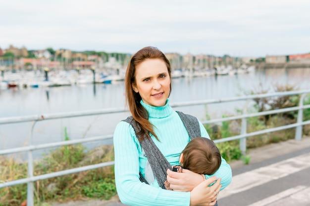 Ritratto di giovane donna adulta che porta il suo bambino di un anno con un porto sullo sfondo nell'area portuale in mare
