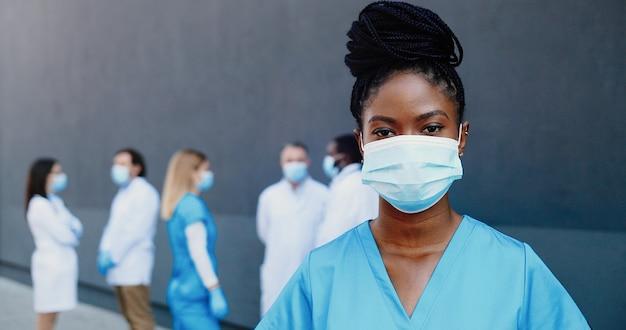 Ritratto di giovane medico afroamericano bella donna nella mascherina medica che guarda l'obbiettivo. primo piano di donna medico nella protezione delle vie respiratorie. colleghi medici di razze miste sullo sfondo.