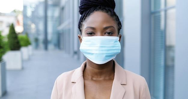 Ritratto di giovane bella donna afroamericana in giacca rosa che toglie la mascherina medica e sorride alla macchina fotografica all'aperto. attraente imprenditrice allegra in strada vicino al centro business in quarantena.