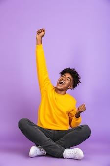 Ritratto di giovane ragazzo afroamericano che sorride e si rallegra mentre è seduto sul pavimento con le gambe incrociate, isolato su sfondo viola