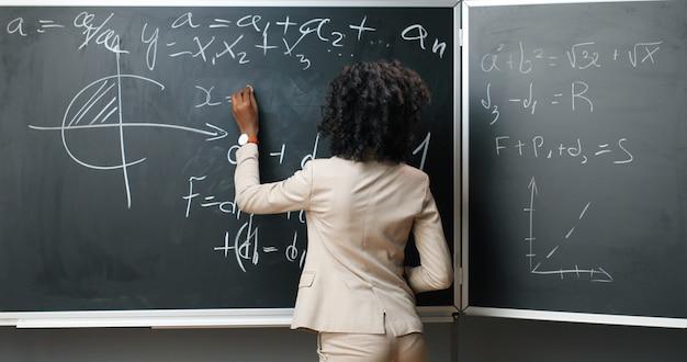Ritratto di giovane insegnante femminile afroamericana in bicchieri in piedi a bordo, scrivendo con il gesso leggi e formule di matematica o fisica e sorridendo alla telecamera in classe. concetto di educazione.