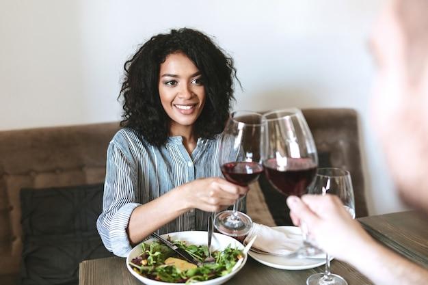 Ritratto di giovane ragazza afroamericana in ristorante con un bicchiere di vino rosso in mano e insalata sul tavolo. bella ragazza sorridente con i capelli ricci scuri seduti al bar e bere vino con un amico