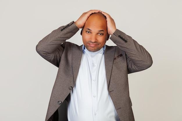 Ritratto di un giovane uomo d'affari afroamericano, tenendo le mani sulla testa, espressione del viso stanca a causa di mal di testa dopo una dura giornata di lavoro.