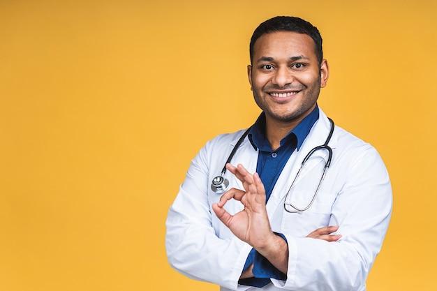 Ritratto di giovane medico nero indiano afroamericano con lo stetoscopio sopra il collo in cappotto medico che sta isolato sopra fondo giallo. ok segno.