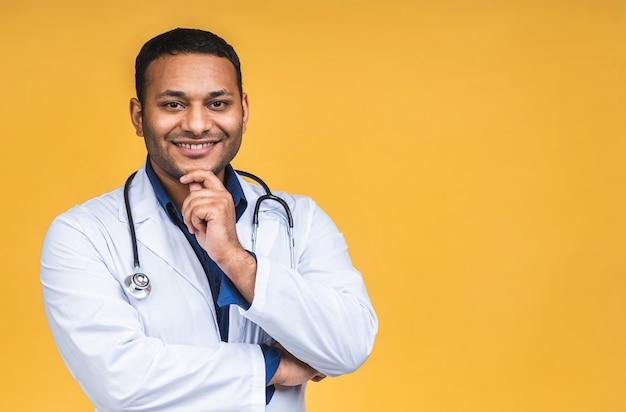 Ritratto di giovane medico nero indiano afroamericano con lo stetoscopio sopra il collo in cappotto medico che sta isolato sopra fondo giallo.