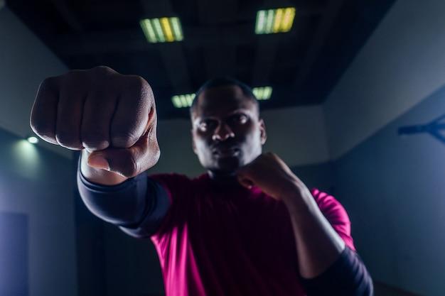 Ritratto di un giovane pugile sportivo afroamericano su pugni sfondo nero palestra pericoloso sguardo minaccioso colpito