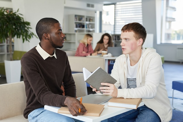 Ritratto di giovane uomo afro-americano a parlare con un amico sul tavolo mentre studiano insieme nella biblioteca del college in preparazione per gli esami