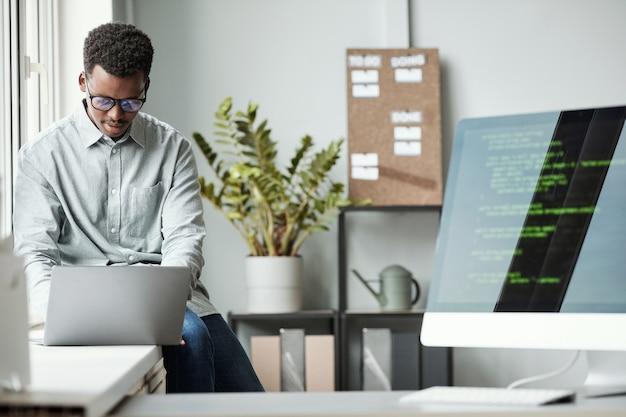 Ritratto di giovane uomo afro-americano che utilizza il laptop mentre è seduto alla finestra nell'ufficio di sviluppo software, schermata del codice in primo piano, spazio di copia