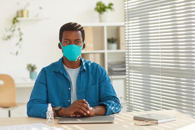 Ritratto di giovane uomo afro-americano che indossa la maschera per il viso seduto al posto di lavoro in ufficio post pandemia