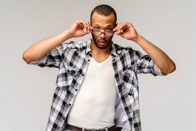 Ritratto di un giovane uomo afroamericano con gli occhiali con espressione sorpresa sul viso