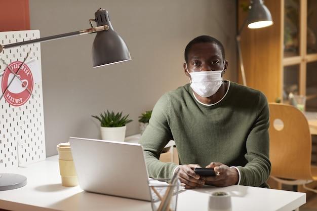 Ritratto di giovane uomo afro-americano che indossa la maschera e guardando la fotocamera mentre è seduto alla scrivania sul posto di lavoro in ufficio, copia dello spazio