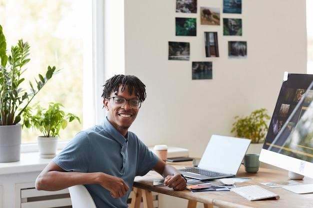 Ritratto di giovane fotografo afro-americano che sorride alla macchina fotografica mentre posa alla scrivania con software di fotoritocco sullo schermo del computer, copia dello spazio