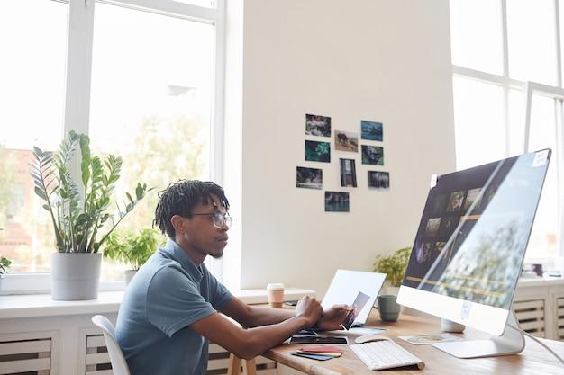 Ritratto di giovane fotografo afro-americano utilizzando il computer alla scrivania in ufficio a casa con software di fotoritocco sullo schermo, copia dello spazio