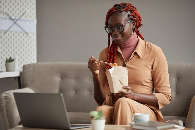Ritratto di giovane donna afro-americana che mangia cibo da asporto e guardando lo schermo del laptop mentre vi rilassate in ufficio a casa, copia dello spazio