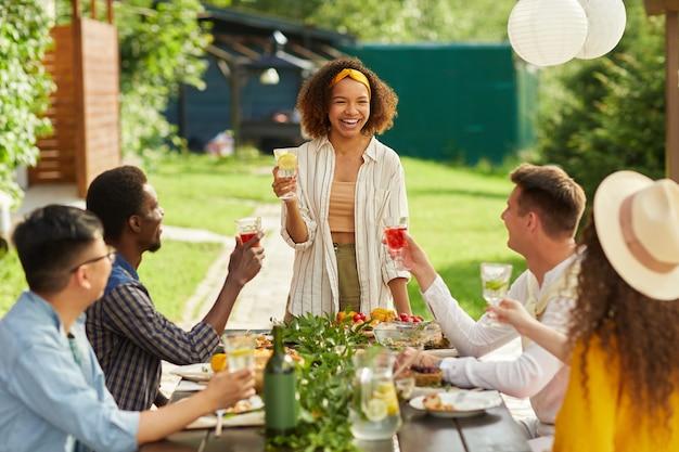 Ritratto di giovane donna afro-americana che ride allegramente mentre si gusta la cena con gli amici sulla terrazza all'aperto in estate