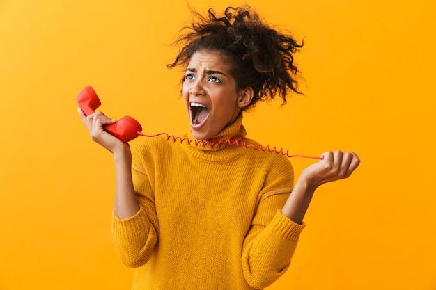 Ritratto di giovane donna afroamericana con acconciatura afro che urla mentre parla sul ricevitore rosso, isolato