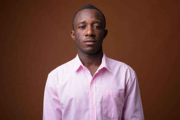 Ritratto di giovane uomo d'affari africano contro il muro marrone