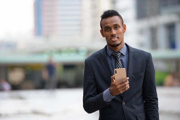 Ritratto di giovane uomo d'affari africano nelle strade della città all'aperto