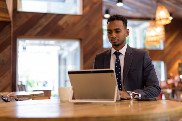 Ritratto di giovane uomo d'affari africano rilassante all'interno della caffetteria