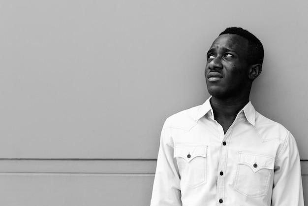 Ritratto di giovane uomo d'affari africano rilassante nelle strade all'aperto in bianco e nero