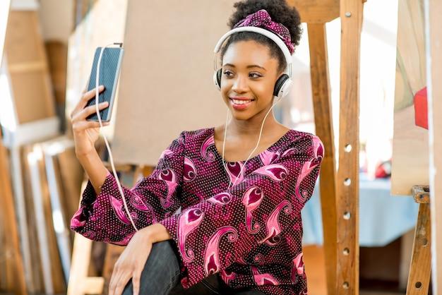 Ritratto di un giovane studente di etnia africana seduto sul pavimento in studio per dipingere