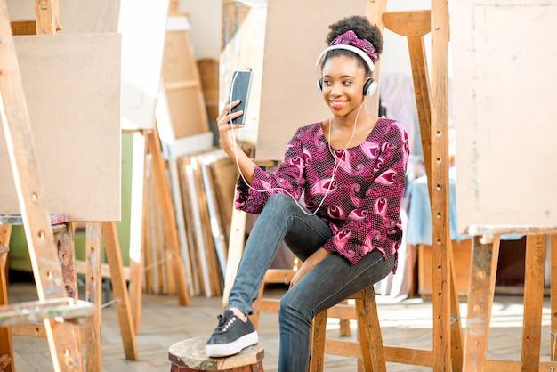 Ritratto di un giovane studente di etnia africana seduto con il telefono durante la pausa in studio per dipingere