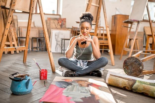 Ritratto di un giovane studente di etnia africana con pittura di natura morta presso lo studio universitario. donna fuori fuoco