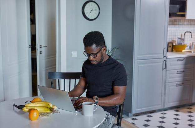 Ritratto di giovane uomo africano concentrato sul lavoro a casa