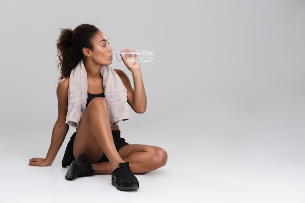 Ritratto di una giovane sportiva africana che riposa dopo l'allenamento isolato sopra il muro grigio, acqua potabile