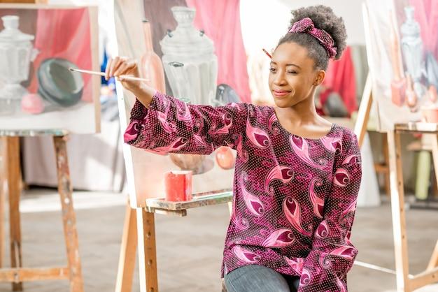 Ritratto di un giovane studente africano seduto in studio per dipingere