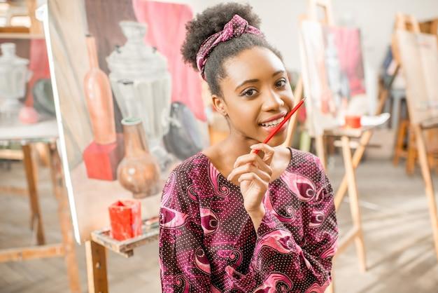 Ritratto di un giovane studente africano seduto con la pittura di natura morta allo studio
